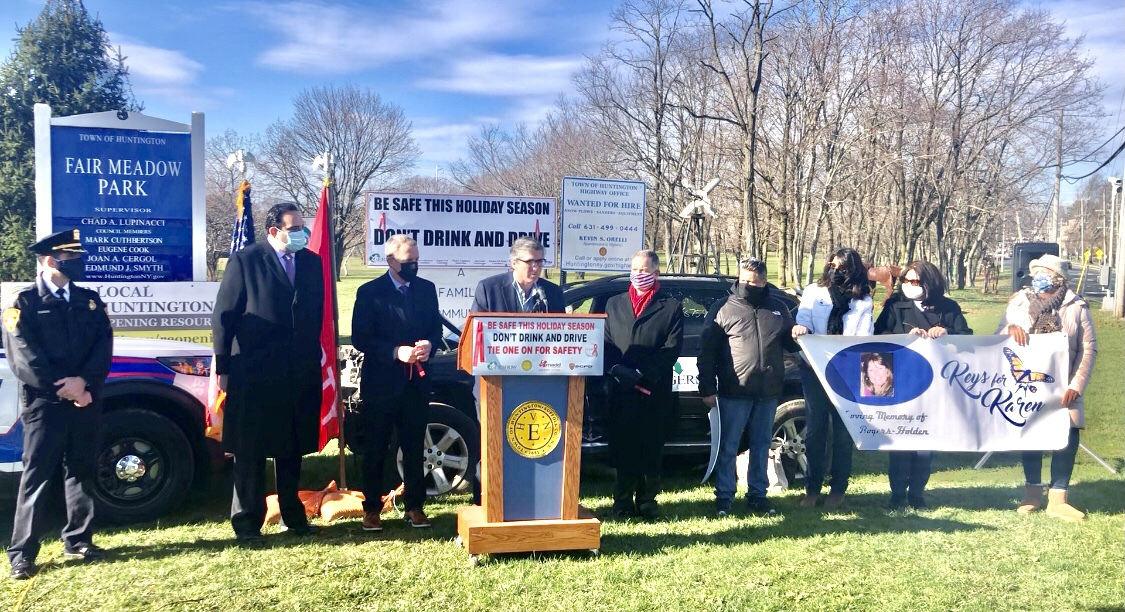 Kevin Gershowitz (standing behind podium), President, Gershow Recycling, speaks during a press conference announcing the Town of Huntington's anti-drunk and distracted driving campaign on December 7. Also pictured (left to right): William Scrima, Officer, Suffolk County Police Department; Chad Lupinacci, Supervisor, Town of Huntington; Mark Cuthbertson and Edmund J.M. Smyth, Council Members, Town of Huntington; William Holden, husband of Karen Holden, who was killed by a drunk driver; Joanne Sperando, Ms. Holden's friend; Lynne Rogers Pallmeyer, Ms. Holden's sister; and Liisa Anderson, Ms. Holden's cousin.